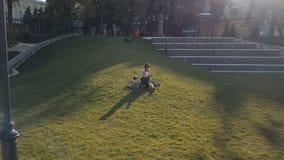 Ciclista de la mujer que miente en hierba verde en parque y que usa el teléfono móvil almacen de metraje de vídeo