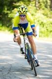 Ciclista del deporte profesional que monta una bici en un camino abierto abajo de la colina en un día de verano caliente Foto de archivo