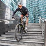 Ciclista del deportista en la bicicleta abajo de las escaleras en fondo urbano Fotos de archivo