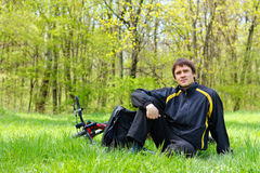 Ciclista del hombre que se sienta en hierba verde Imagen de archivo