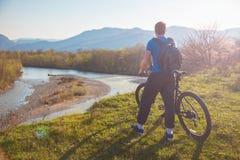 Ciclista del muchacho que se coloca en una montaña y miradas en el río en el concepto de la puesta del sol para los viajeros Visi Fotografía de archivo