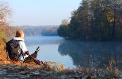 Ciclista della donna che si siede sulla riva del fiume che gode della ricreazione Fotografie Stock Libere da Diritti