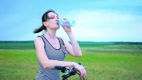 Ciclista della giovane donna sull'acqua potabile del mountain bike durante il colpo medio all'aperto di riciclaggio di allenament video d archivio