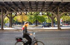 Ciclista do borrão que veste um capacete que biking sob uma ponte em uma rua em Berlim, Alemanha imagem de stock royalty free