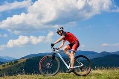 Ciclista do desportista do atleta na bicicleta de montada profissional do sportswear e do corta-mato do capacete fotos de stock royalty free