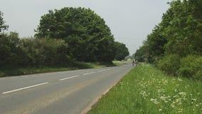 Ciclista dos que monta abajo de una carretera nacional almacen de video