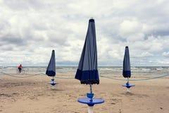 Ciclista e guarda-chuvas na praia do mar Báltico Fotografia de Stock