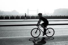 Ciclista e pareggiatore sul ponte di Londra, Londra, Regno Unito fotografia stock libera da diritti