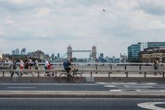 Ciclista e pedoni sul ponte di Londra, Londra, Regno Unito fotografia stock
