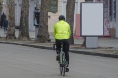 Ciclista em uma bicicleta de competência fora na cidade Anunciando o citylight com lugar claro do anúncio fotografia de stock royalty free