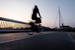 Ciclista em uma ponte da bicicleta em Odense, Dinamarca imagens de stock