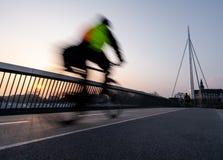 Ciclista em uma ponte da bicicleta em Odense, Dinamarca imagem de stock