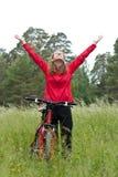 Ciclista emocionado de la mujer con las manos outstretched Imagenes de archivo