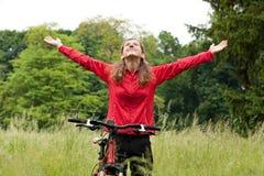 Ciclista emocionado de la mujer con las manos outstretched Fotos de archivo libres de regalías