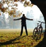 Ciclista emocionado de la mujer que se coloca en un parque Fotos de archivo libres de regalías