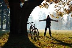 Ciclista emocionado de la mujer que se coloca en un parque con las manos outstretched Imagen de archivo libre de regalías