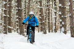 Ciclista en el azul que monta la bici de montaña en el invierno hermoso Forest Extreme Sport y el concepto Biking de Enduro Foto de archivo libre de regalías