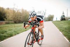 Ciclista en el casco y la ropa de deportes, entrenamiento de la bicicleta foto de archivo libre de regalías