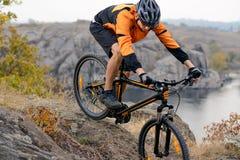 Ciclista en el desgaste anaranjado que monta la bici abajo Rocky Hill debajo del río Foto de archivo libre de regalías