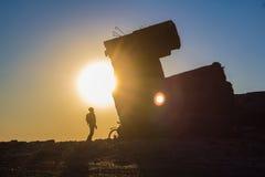 Ciclista en el fondo de la puesta del sol Foto de archivo