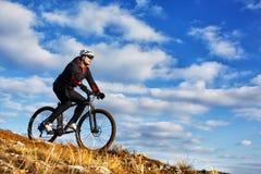 Ciclista en el rastro hermoso del prado el día soleado fotografía de archivo