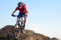 Ciclista en el rojo que monta la bici abajo de la roca en el fondo del cielo azul Deporte extremo y concepto Biking de Enduro Fotografía de archivo libre de regalías