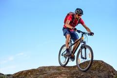 Ciclista en el rojo que monta la bici abajo de la roca en el fondo del cielo azul Deporte extremo y concepto Biking de Enduro Fotografía de archivo