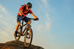 Ciclista en el rojo que monta la bici abajo de la roca en el fondo del cielo azul Deporte extremo y concepto Biking de Enduro Imágenes de archivo libres de regalías