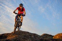 Ciclista en el rojo que monta la bici abajo de la roca en el fondo del cielo azul Deporte extremo y concepto Biking de Enduro Imagen de archivo