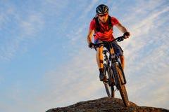 Ciclista en el rojo que monta la bici abajo de la roca en el fondo del cielo azul Deporte extremo y concepto Biking de Enduro Fotos de archivo