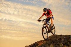 Ciclista en el rojo que monta la bici abajo de la roca en la puesta del sol Deporte extremo y concepto Biking de Enduro Foto de archivo