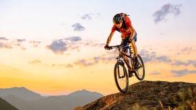 Ciclista en el rojo que monta la bici abajo de la roca en la puesta del sol Deporte extremo y concepto Biking de Enduro imagen de archivo