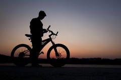 Ciclista en fondo de la ciudad en la puesta del sol Imagen de archivo libre de regalías