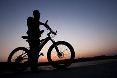 Ciclista en fondo de la ciudad en la puesta del sol Fotografía de archivo