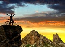 Ciclista en la bici en la puesta del sol Foto de archivo libre de regalías