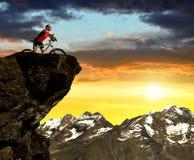 Ciclista en la bici en la puesta del sol imagenes de archivo