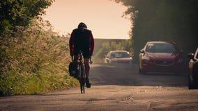 Ciclista en la carretera nacional en la puesta del sol metrajes