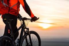 ciclista en la montaña-bici en la puesta del sol, ciclista en el fondo de la puesta del sol hermosa Imágenes de archivo libres de regalías