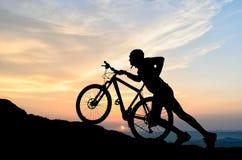 Ciclista en la puesta del sol Imagenes de archivo