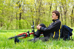 Ciclista felice dell'uomo con la bici che si siede sull'erba verde Immagine Stock