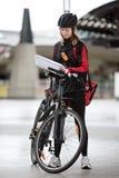Ciclista femenino con el mensajero Bag And Package encendido Imagen de archivo libre de regalías