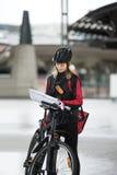 Ciclista femenino con el mensajero Bag And Package encendido Foto de archivo libre de regalías