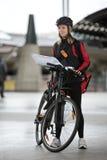 Ciclista femenino con el mensajero Bag And Package encendido Imagen de archivo