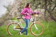 Ciclista femenino con la bicicleta blanca del vintage en jardín de la primavera Fotografía de archivo