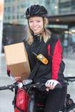 Ciclista femenino con la caja de cartón y el mensajero Bag Fotografía de archivo