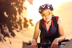 Ciclista femenino en bicicleta del montar a caballo de la ropa de deportes imagen de archivo
