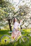 Ciclista femenino hermoso con la bicicleta retra en el jardín de la primavera Imágenes de archivo libres de regalías