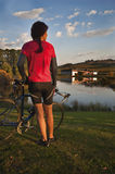 Ciclista femenino por el lago del viñedo en el ocaso Imagenes de archivo
