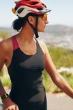 Ciclista femenino que mira lejos Foto de archivo libre de regalías