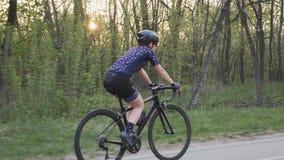 Ciclista femenino que monta una bicicleta en la puesta del sol en el parque Siga la vista lateral Ciclo y concepto del triathlon  almacen de video